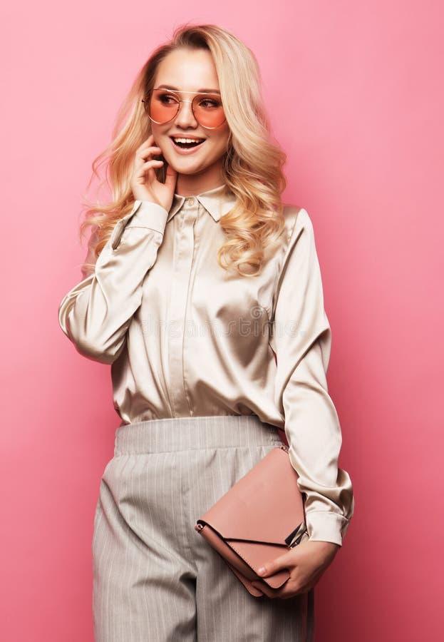 Blusa que lleva, pantalones y gafas de sol de la mujer rubia hermosa joven imagenes de archivo