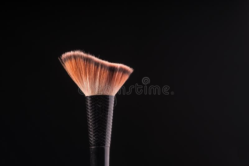 Blush Brush on Black. A makeup brush as part of a cosmetic set is portrayed isolated on a dark backdrop royalty free stock image