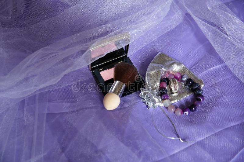 Blush and mirror, brush, ring and bracelet on a purple fabric background. Women`s cosmetics and accessories. stock images