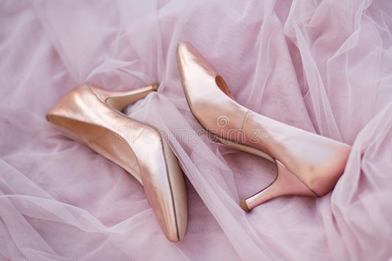 Pink gold bridal shoes. Tender beige satin cloth texture background. Top view of lady`s pumps. Space for text. royalty free stock photography