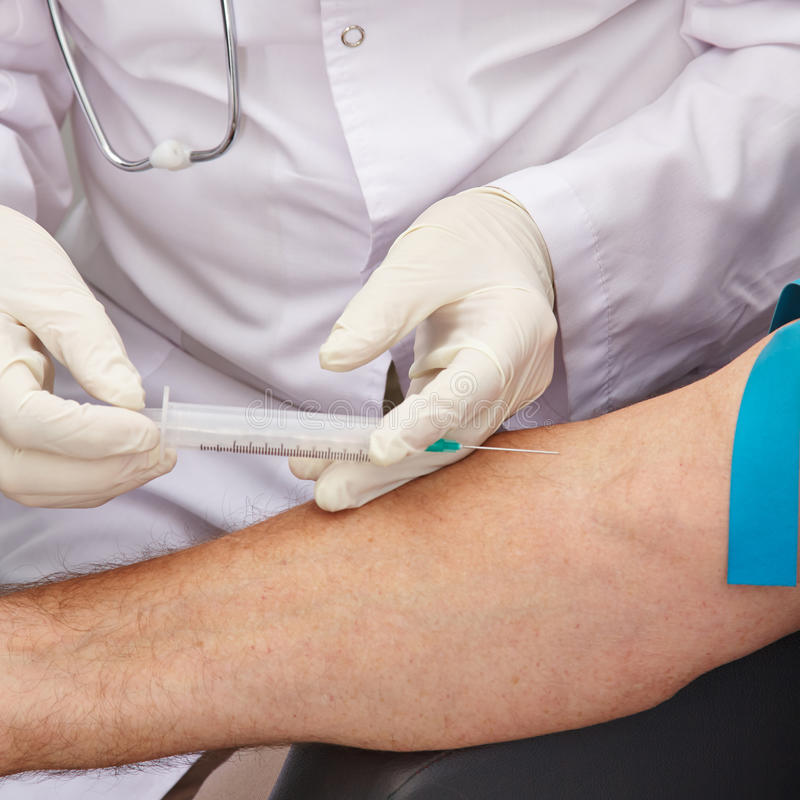 Blut withdrawal on arm with syringe. During a blood donation in a hospital stock image