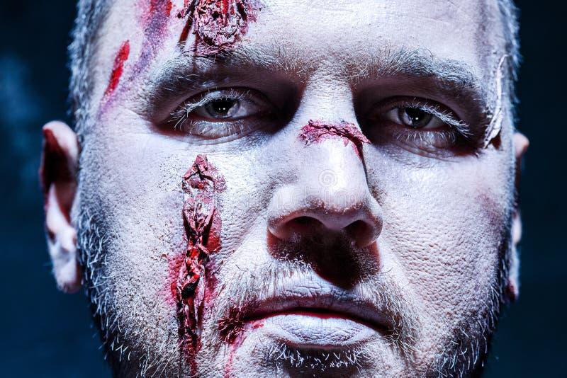 Blutiges Halloween-Thema: verrückter Mörder als junger Mann mit Blut lizenzfreie stockfotos