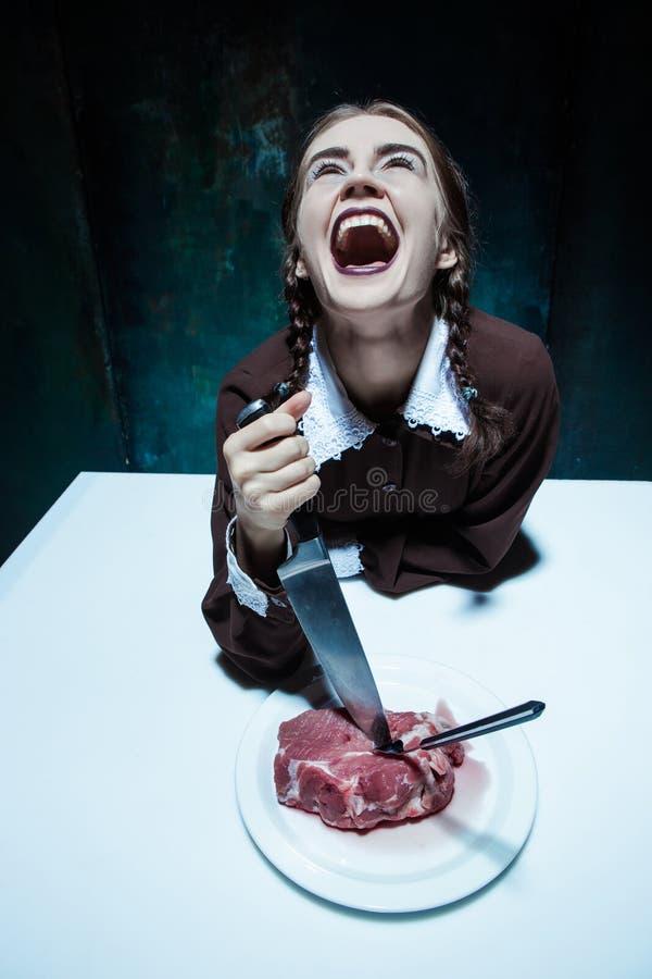 Blutiges Halloween-Thema: verrücktes Mädchen mit einem Messer, einer Gabel und einem Fleisch lizenzfreies stockbild
