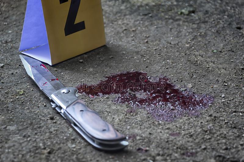 Blutiges Messer und kriminelle Markierungen auf dem Boden, Tötungsbeweis C lizenzfreies stockbild