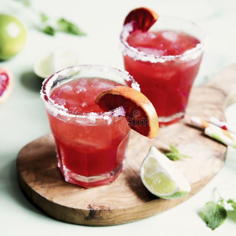 Blutorange und Kalk Margaritacocktail mit Scheiben der frischen Frucht und des Eises auf optimistischem grünem Hintergrund stockfotos