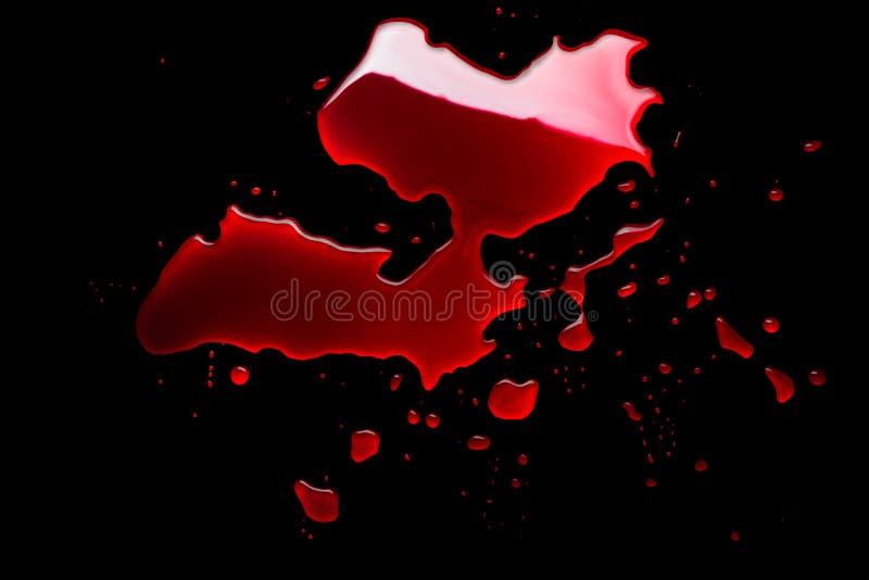 Blutpfütze auf einem schwarzen Hintergrund stockfoto