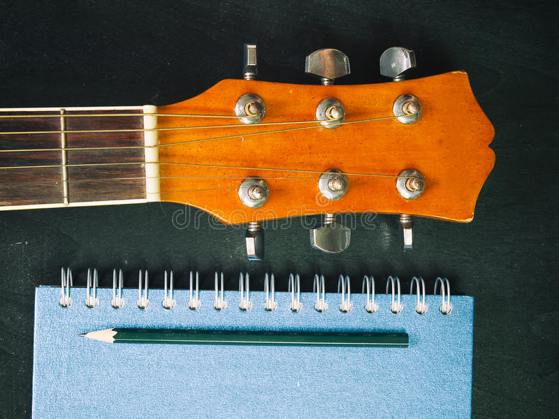 Blyertspenna, bok och gitarr royaltyfri fotografi