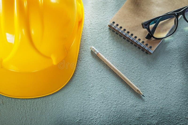 Blyertspenna för anteckningsbok för byggnadshjälmexponeringsglas på konkret bakgrund arkivbilder