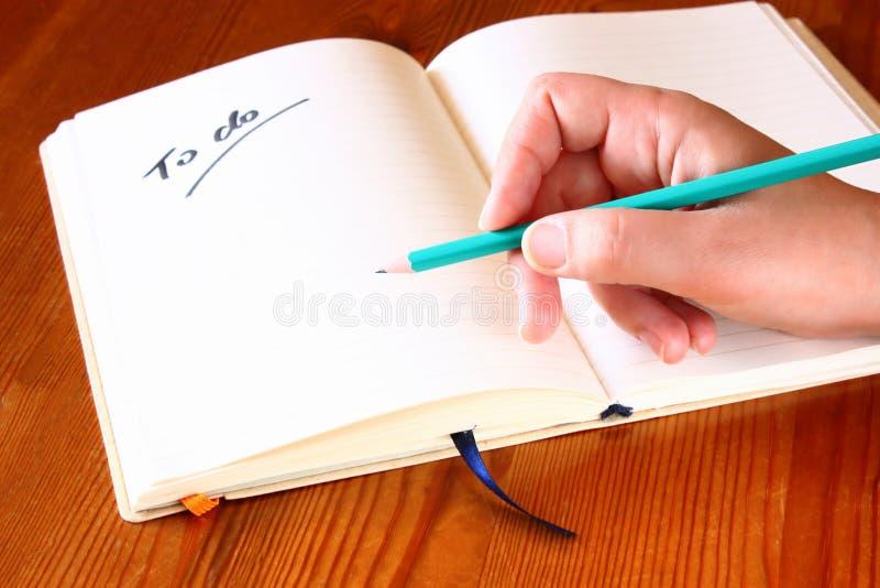 Blyertspenna för kvinnahandinnehav och öppnad anteckningsbok med a som gör listan. royaltyfria foton