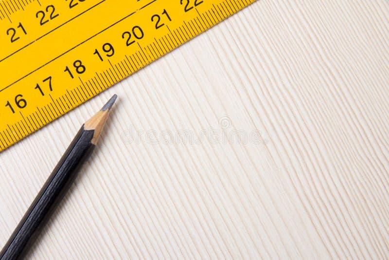 Blyertspenna och linjalcloseup på träbräde arkivfoton