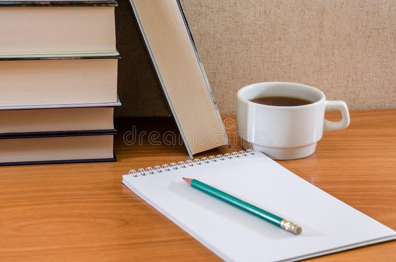 Blyertspenna på en anteckningsbok, böcker och en kopp te på tabellen arkivbild