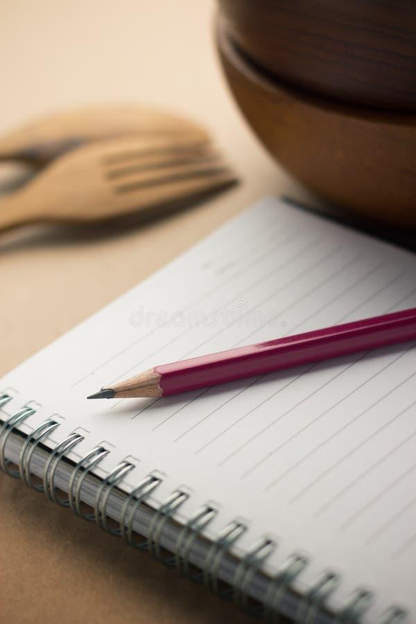Blyertspenna som lägger på anteckningsboken royaltyfri bild