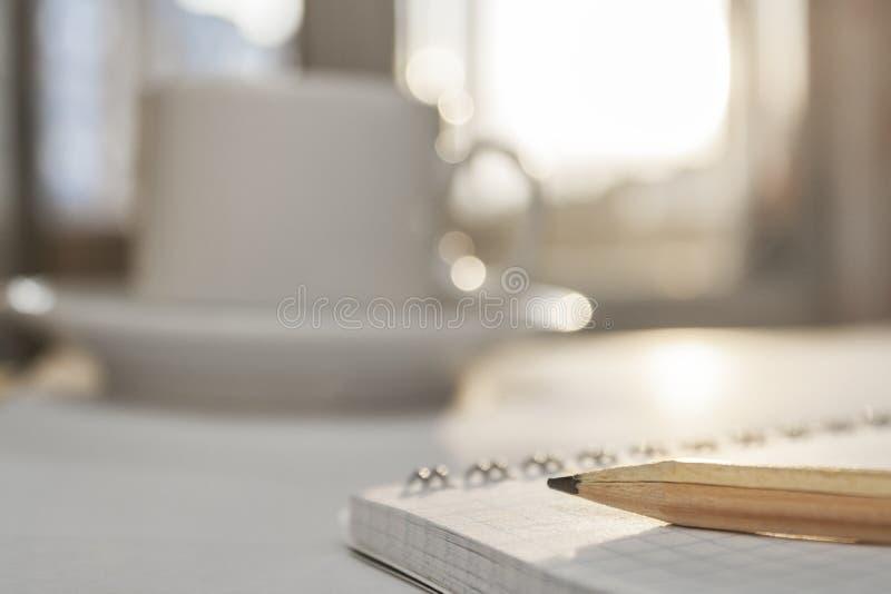 Blyertspenna som ligger på en anteckningsbok Skrivbordanseende nära ett fönster arkivbilder