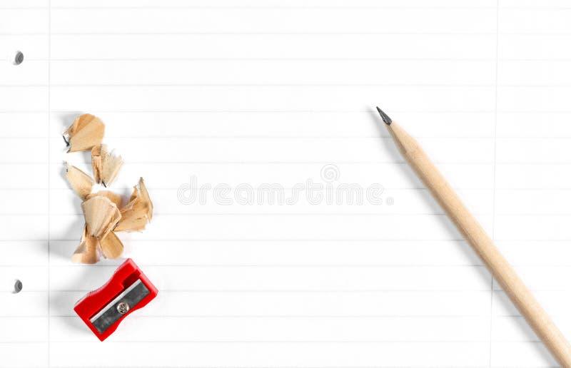Blyertspenna som v?ssar shavingsskolbokbakgrund arkivfoto
