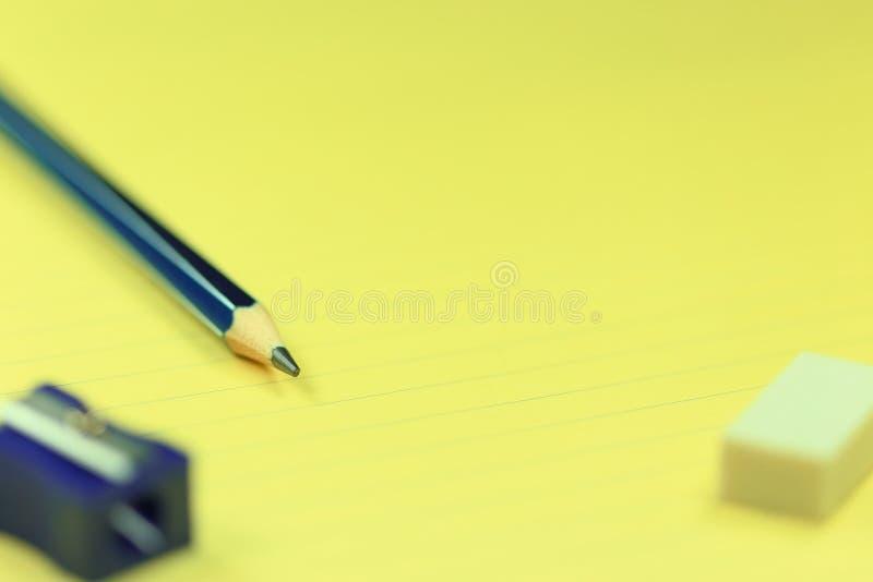Blyertspenna, vässare, radergummi och papper royaltyfri foto