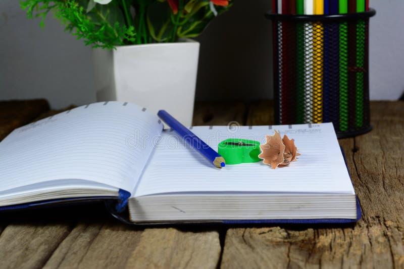 blyertspennafallet, blått ritar, den öppnade anteckningsboken arkivbilder