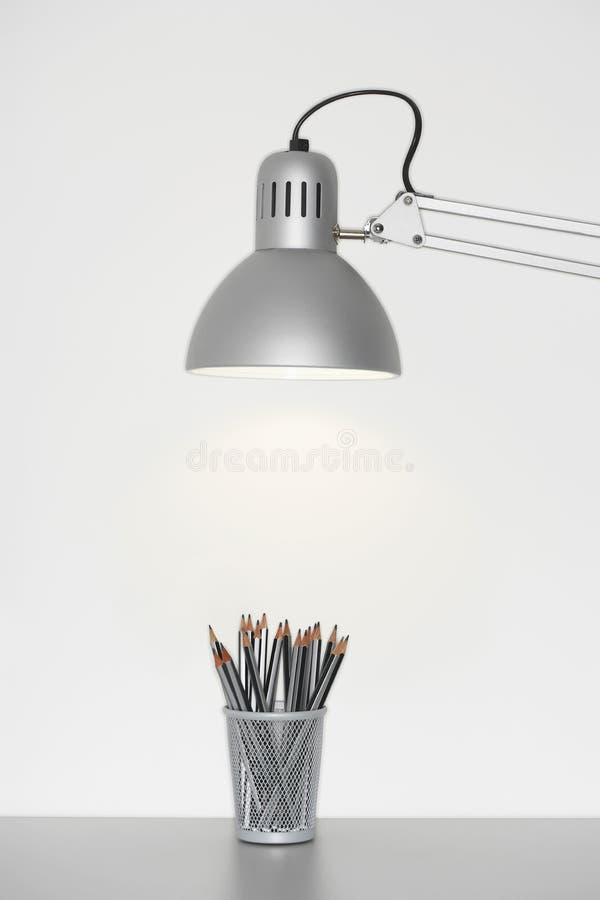 Blyertspennahållare under den justerbara lampan arkivbilder
