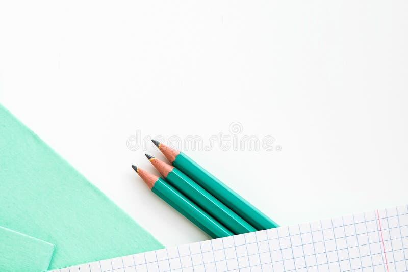 Blyertspennor bredvid skolaanteckningsboken arkivbilder