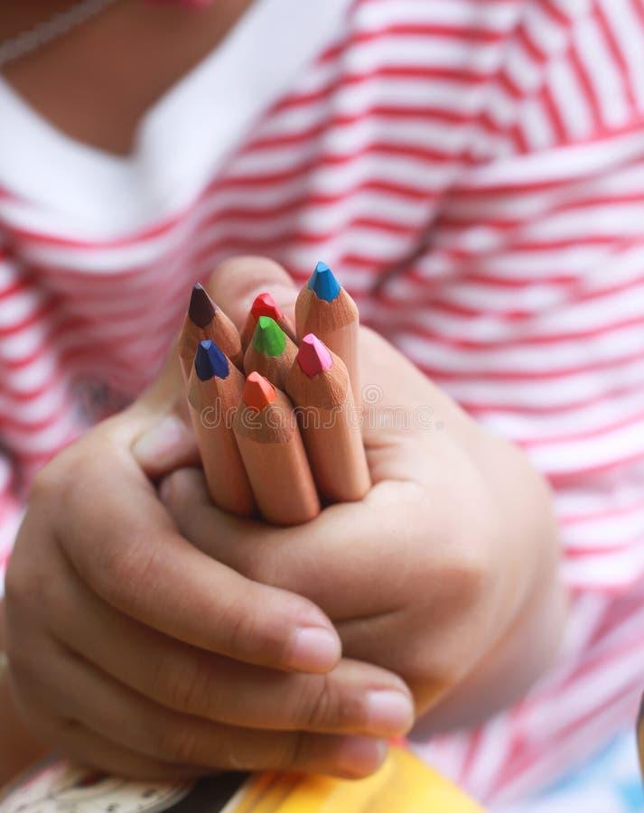 Blyertspennor för barnhållfärg på den lilla handen arkivfoto
