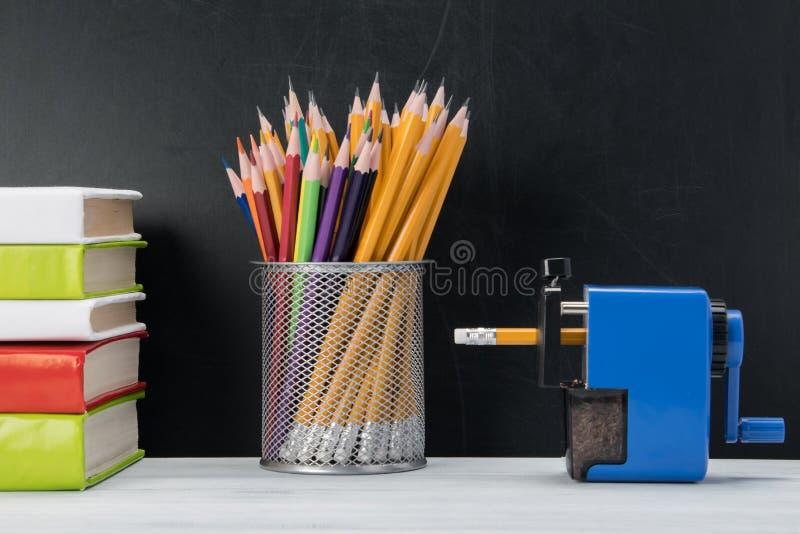 Blyertspennor i ett exponeringsglas, böcker och vässaren som står på en ljus tabell på en svart bakgrund arkivfoton