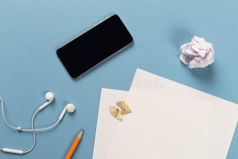 Blyertspennor med att vässa shavings med vitbokark på färgad backgroung, kontorshjälpmedel, rullade papper, telefon med hörlurar fotografering för bildbyråer