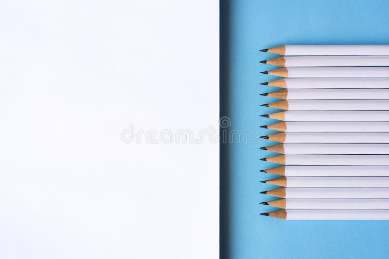 Blyertspennor och en anteckningsbok p? bl? bakgrund arkivfoton