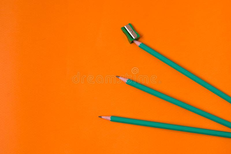Blyertspennor och vässare på orange bakgrund royaltyfri fotografi
