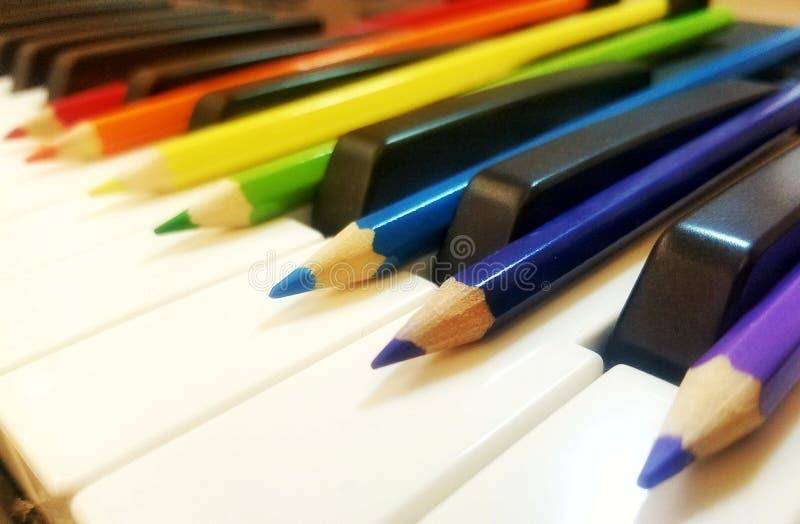 Blyertspennor på pianotangenter fotografering för bildbyråer
