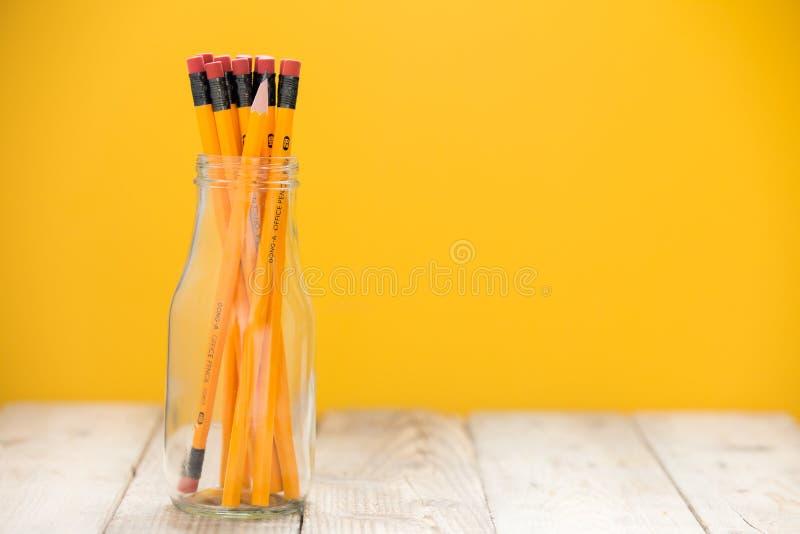 Blyertspennorna i en glass krus på ett trägolv, gul bakgrund arkivbilder