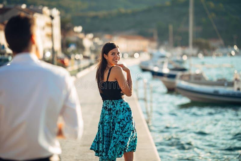 Blyg flirty kvinna som ler till en man Man att ge en komplimang till en inbunden övergående kvinna Motta en komplimang på gatan o royaltyfria foton