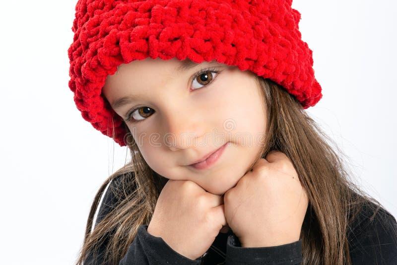 Blyg liten flicka i röd hatt royaltyfria bilder