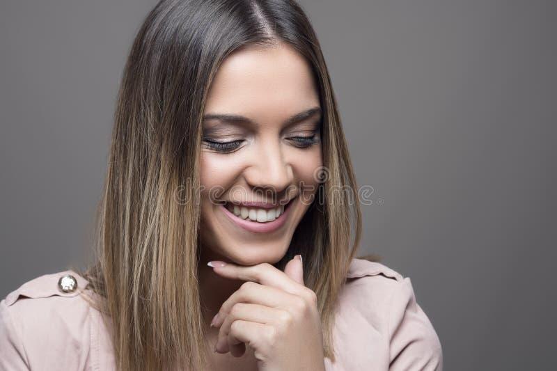 Blyg nätt kvinna som ler med stängda ögon arkivfoton