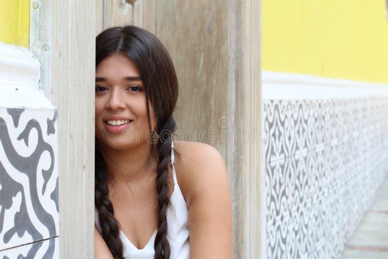 Blyg ung flicka som döljer bak dörr arkivfoto