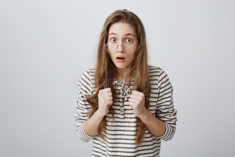 Blyga flickaförsök att stå för henne Stående av den nervösa smarta unga kvinnliga studenten i exponeringsglas som rymmer grep hår royaltyfri foto