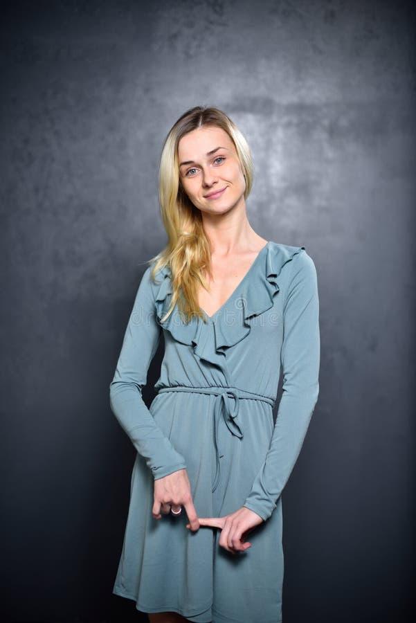 Blygsam blond flicka på en grå väggbakgrund royaltyfri bild