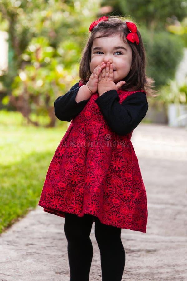 Blygt lyckligt och att le lilla barnet behandla som ett barn flickan som fnissar och skrattar fotografering för bildbyråer