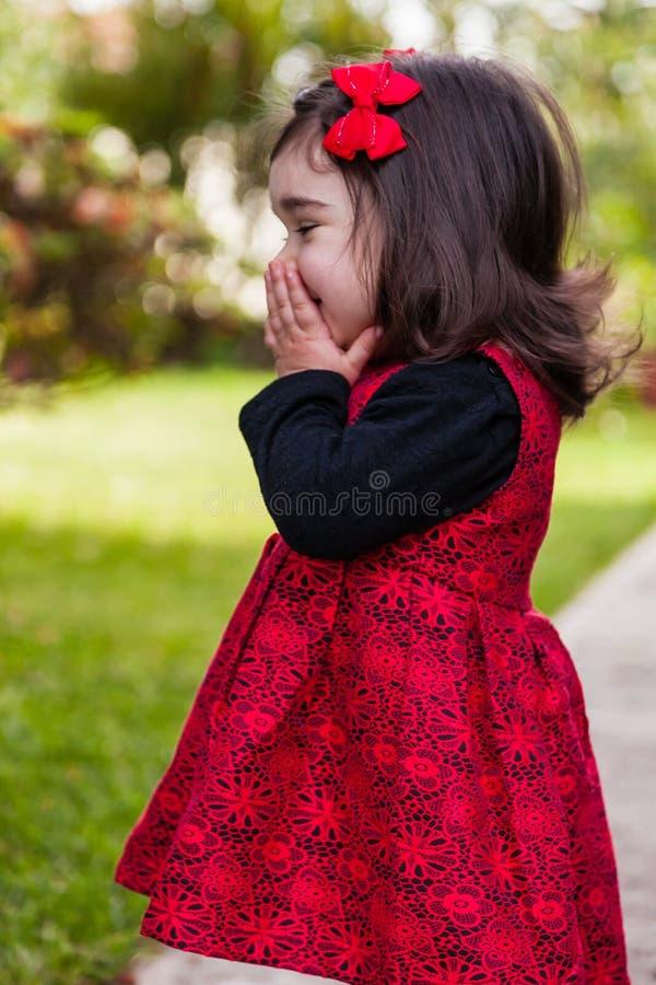 Blygt lyckligt och att le lilla barnet behandla som ett barn flickan som fnissar och skrattar royaltyfri foto
