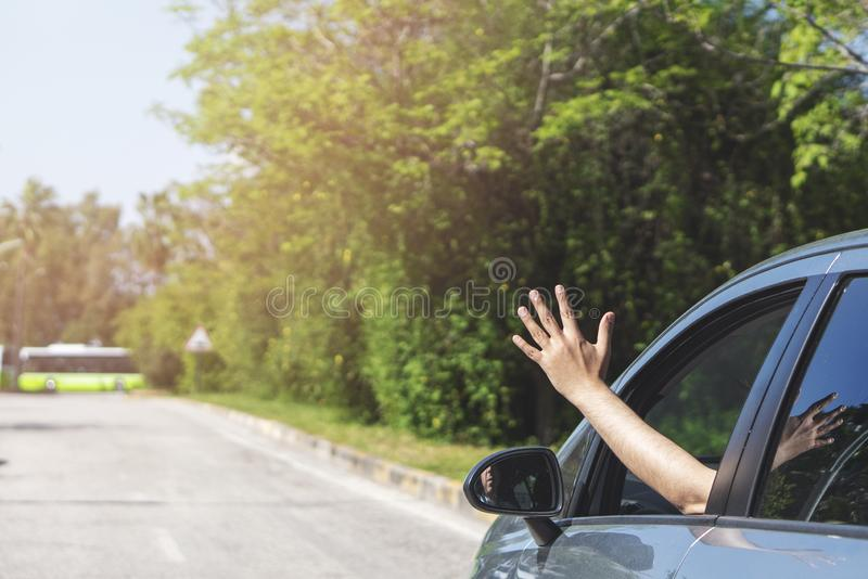 BMan driver feeling the wind through his hands while driving in the city.freedom concept stock photos