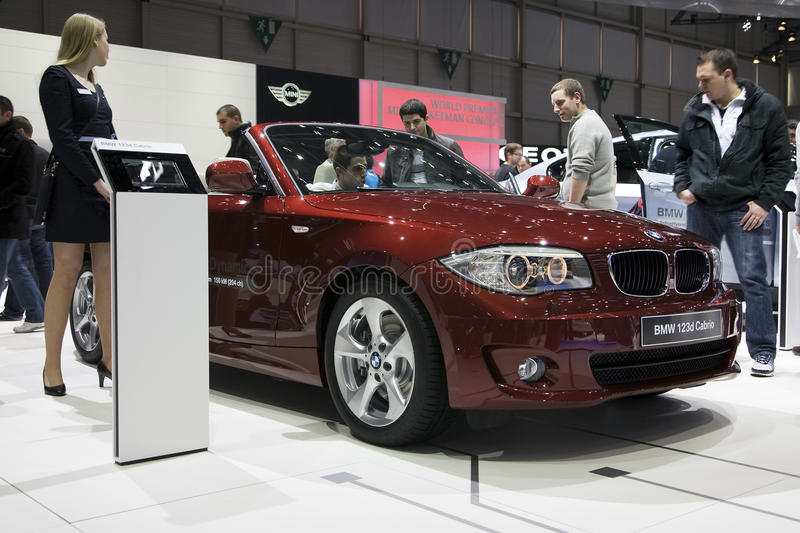 BMW 123d Cabrio. A hostess standing next to the BMW 123d Cabrio at the 2011 Geneva Motor Show. Photo taken on: March 04th, 2011 royalty free stock image