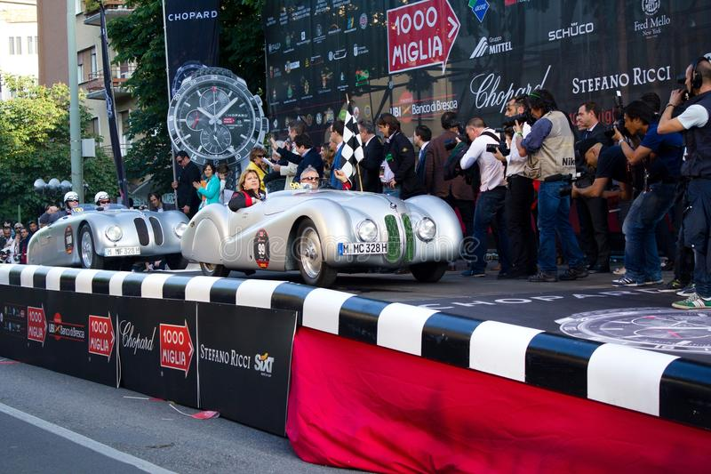 BMW 328 roadster at the start of 2012 1000 Miglia. BRESCIA ITALY - MAY 17: silver 1939 BMW 328 roadster driven by G. Can� starts the 1000 Miglia 2012, on royalty free stock photography