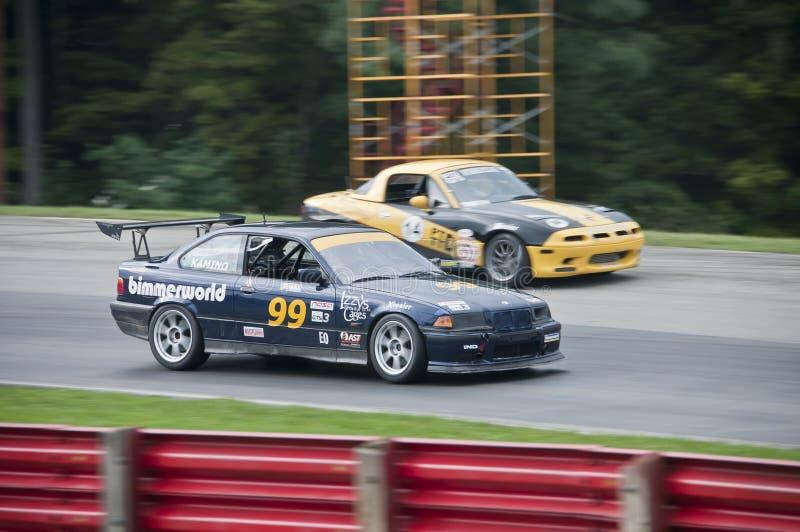 Гоночный автомобиль BMW E36. Гоночный автомобиль BMW E36 проезжает мимо другого транспортного средства на чемпионате NASA 2011 года на трассе спортивных автомобилей Mid-Ohio в Лексингтоне, штат Огайо, 10 сентября стоковое изображение без роялти