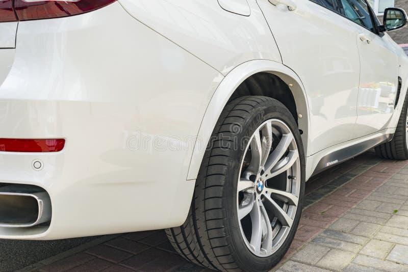 BMW F15 X5 M kapacitet Gummihjul- och legeringshjul Sidosikt av en vit modern lyxig sportbil Bilyttersidadetaljer royaltyfri fotografi