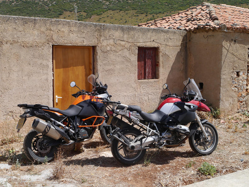 BMW R1200GS and KTM Adventure 1050 beside an outhouse in Greece. Dusty BMW R1200GS and KTM Adventure 1050 beside an outhouse in Greece royalty free stock photography