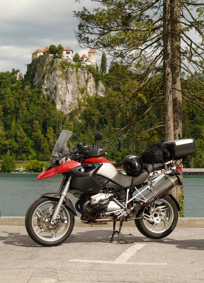 BMW R1200GS at Lake Bled, Slovenia. Red and silver BMW R1200GS at Lake Bled, Slovenia. Pine tree and castle in the background stock photography