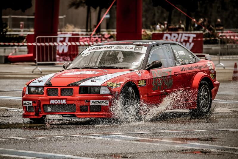 BMW raceauto in actie tegen nat asfalt royalty-vrije stock afbeeldingen