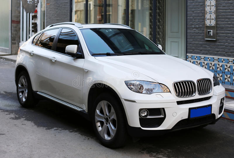 BMW SUV. A white BMW suv with office building royalty free stock photos