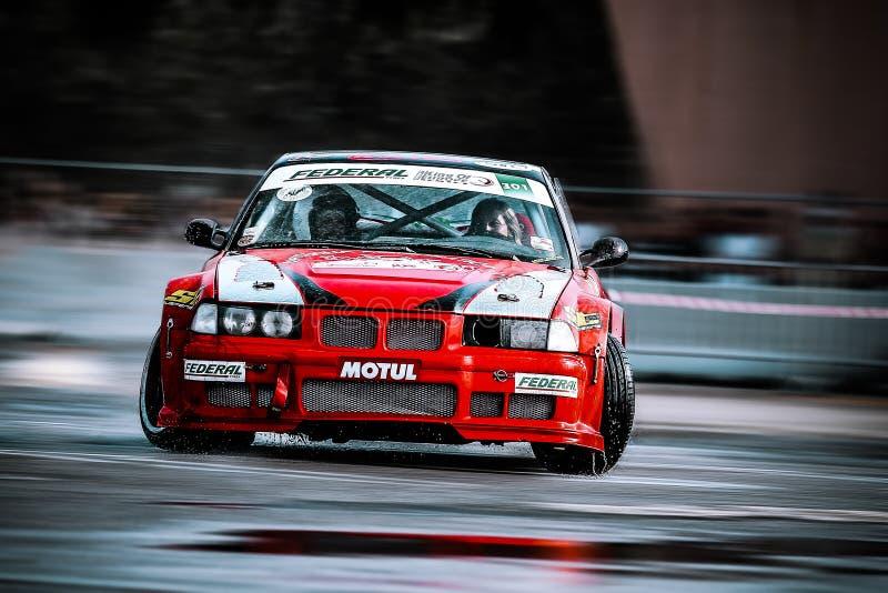 BMW vermelho que deriva no asfalto molhado fotografia de stock