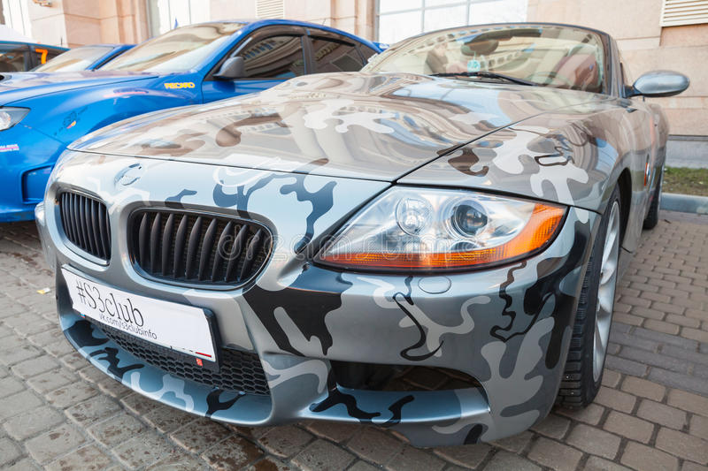 BMW z4 roadster car with camouflage paintings. Saint-Petersburg, Russia - April 11, 2015: BMW z4 roadster car with camouflage color scheme stands parket on the stock image