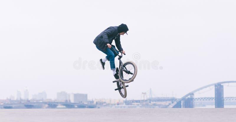 BMX车手做一个TAilwhip把戏 年轻人在天空中的做把戏在BMX自行车 BMX自由式 免版税库存照片