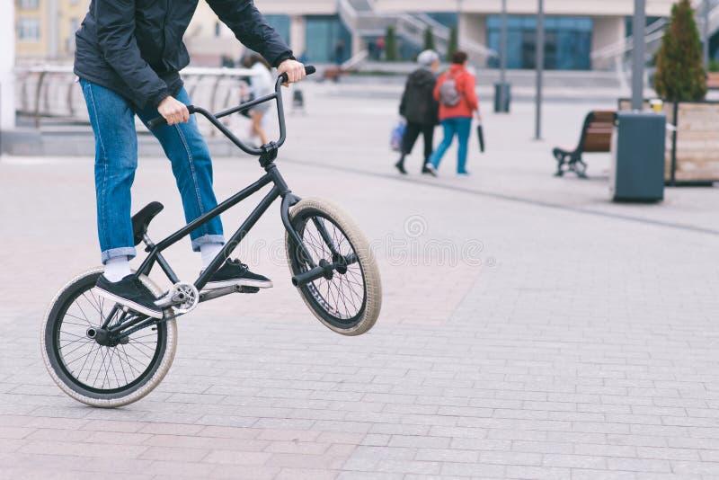 BMX自由式 做把戏的年轻人在BMX自行车的一个公园 在自行车的后面轮子的骑自行车者火车 库存图片